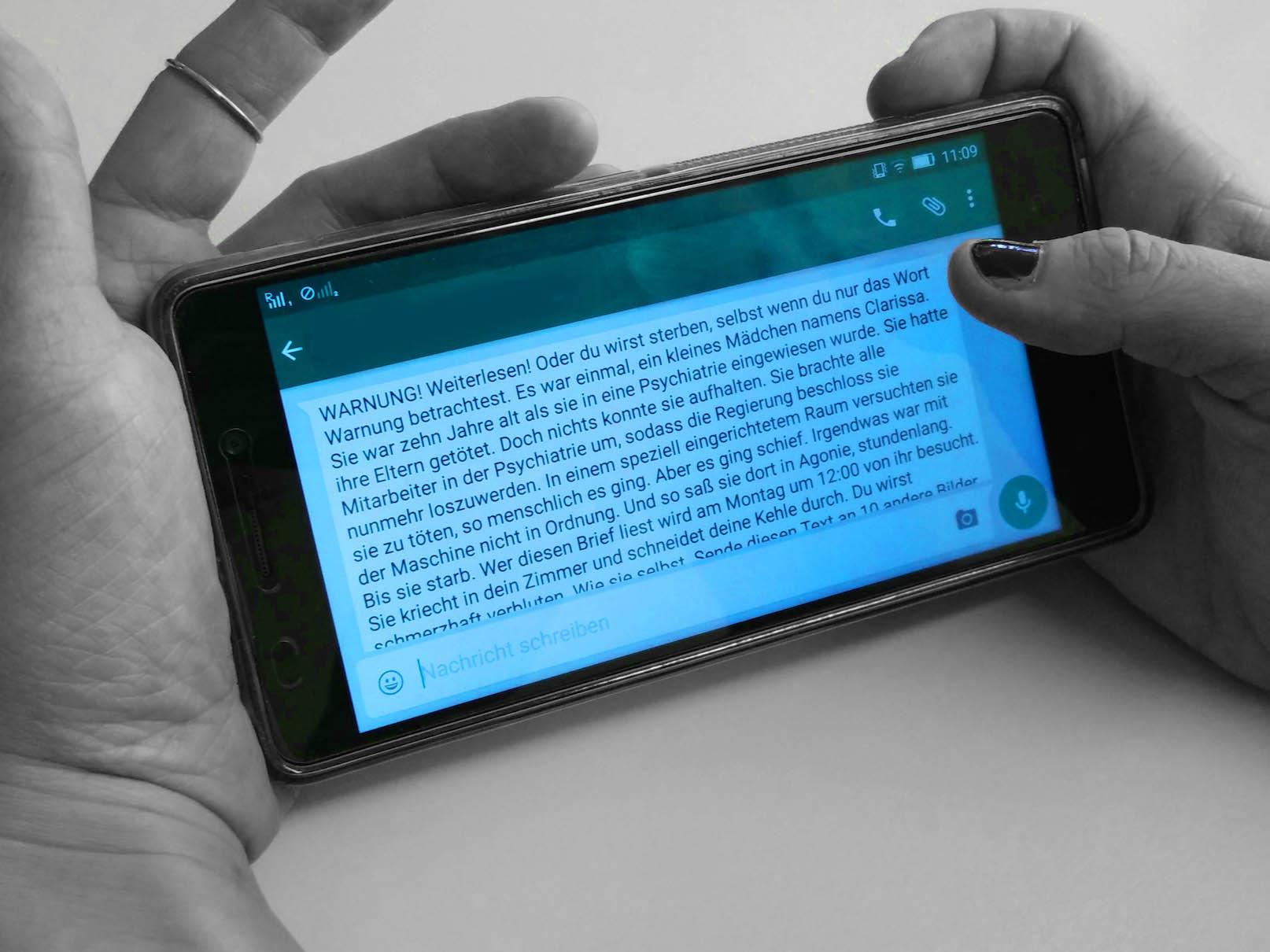 Hand hält Handy mit Kettenbrief