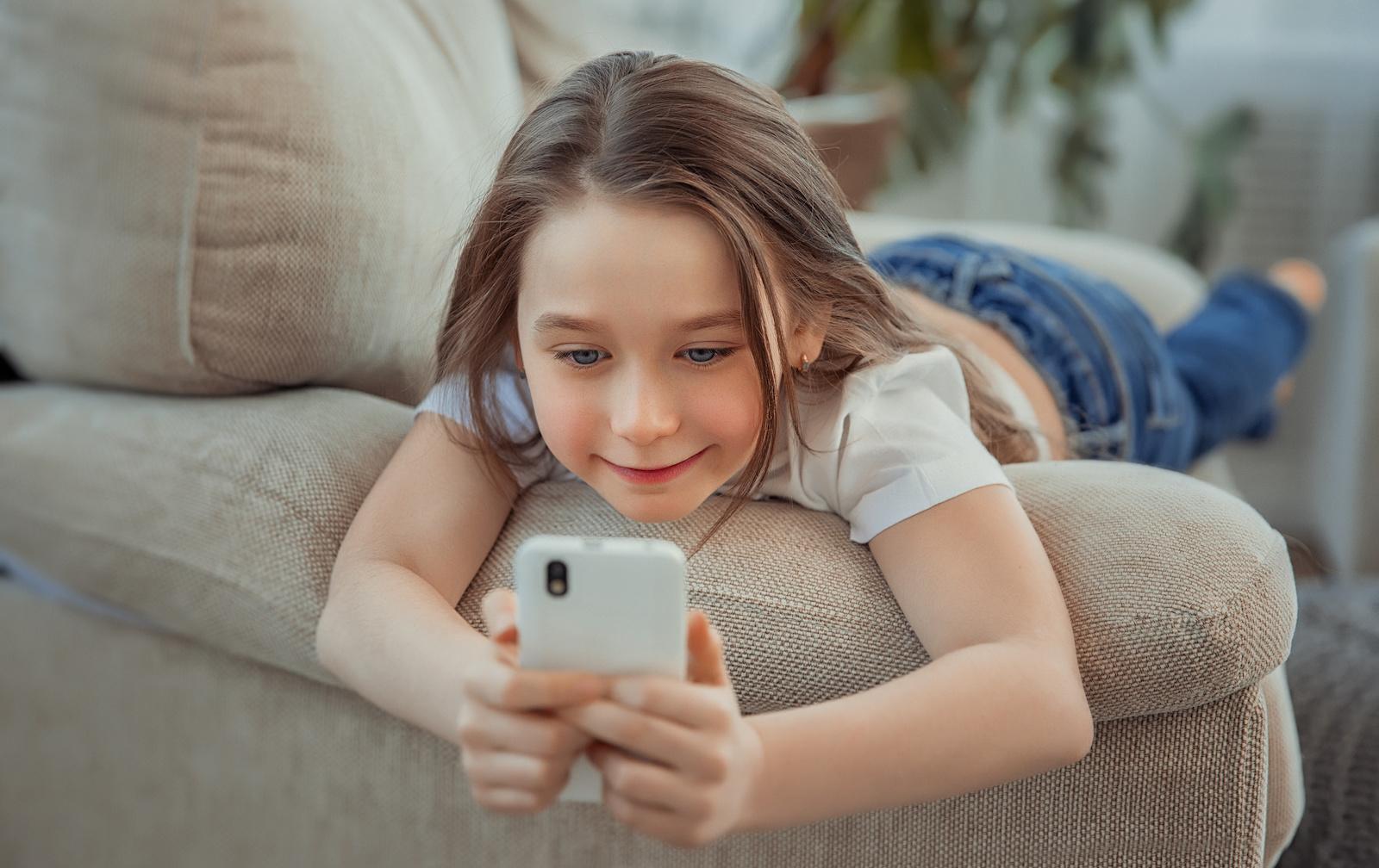 Mädchen liegt auf dem Sofa mit ihrem Smartphone