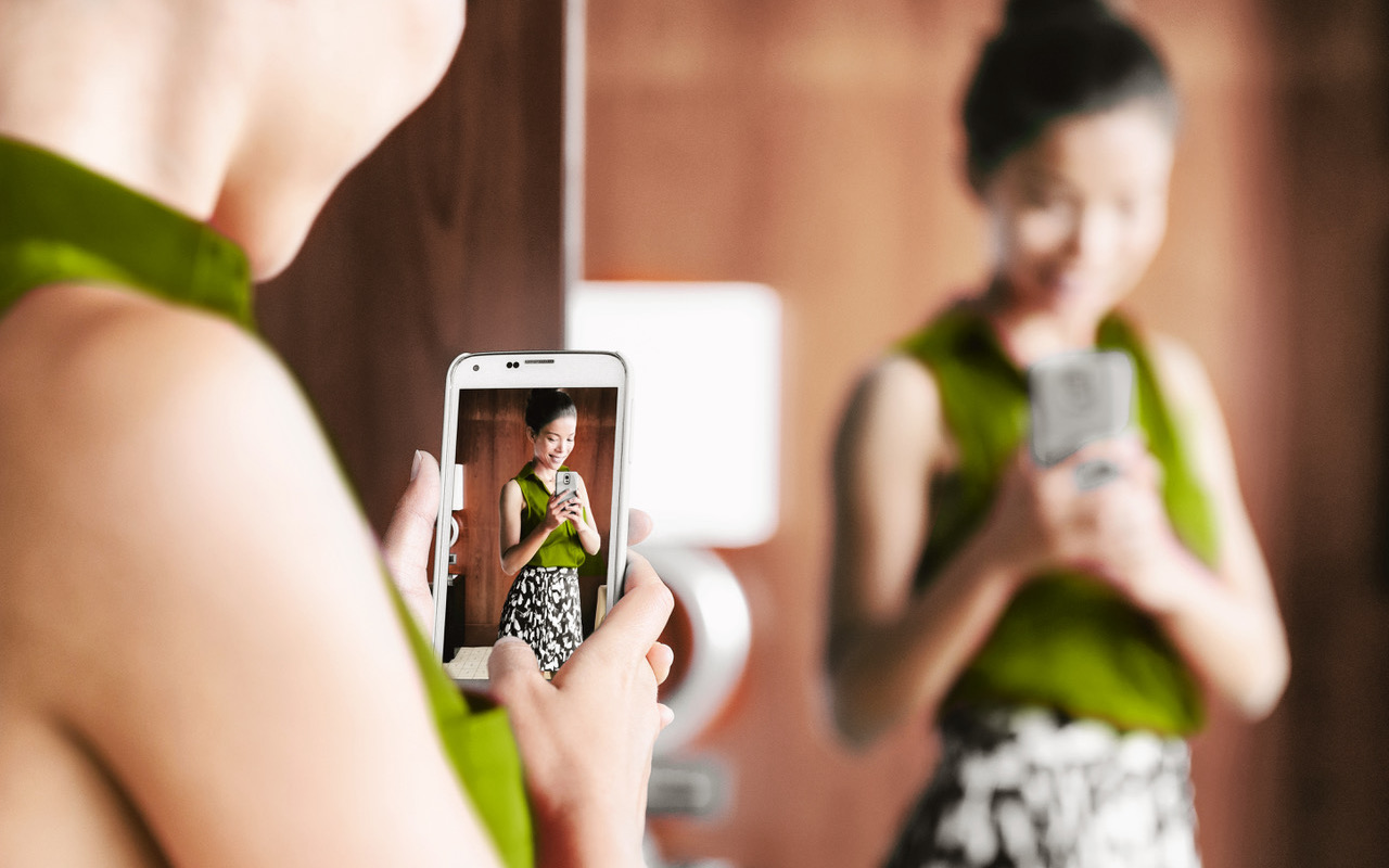 Mirror selfie woman taking picture with mobile phone in store mirror shopping for clothes looking at her fashion oufit for office taking selfies in changing room. Weight loss, body image, self-esteem.